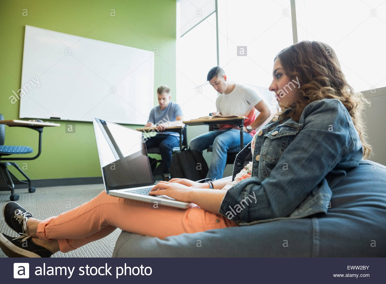 College student using laptop on bean bag chair - Stock Image