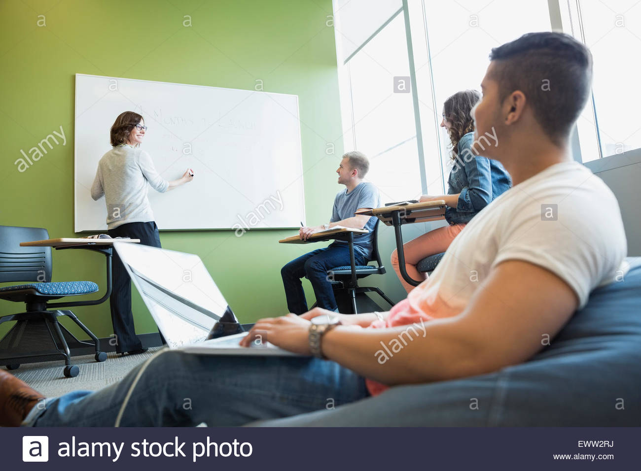 College students watching professor at whiteboard in classroom - Stock Image