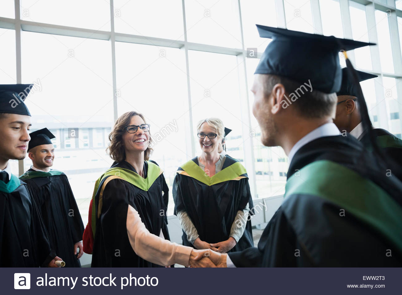 Professor shaking hands with college graduate - Stock Image