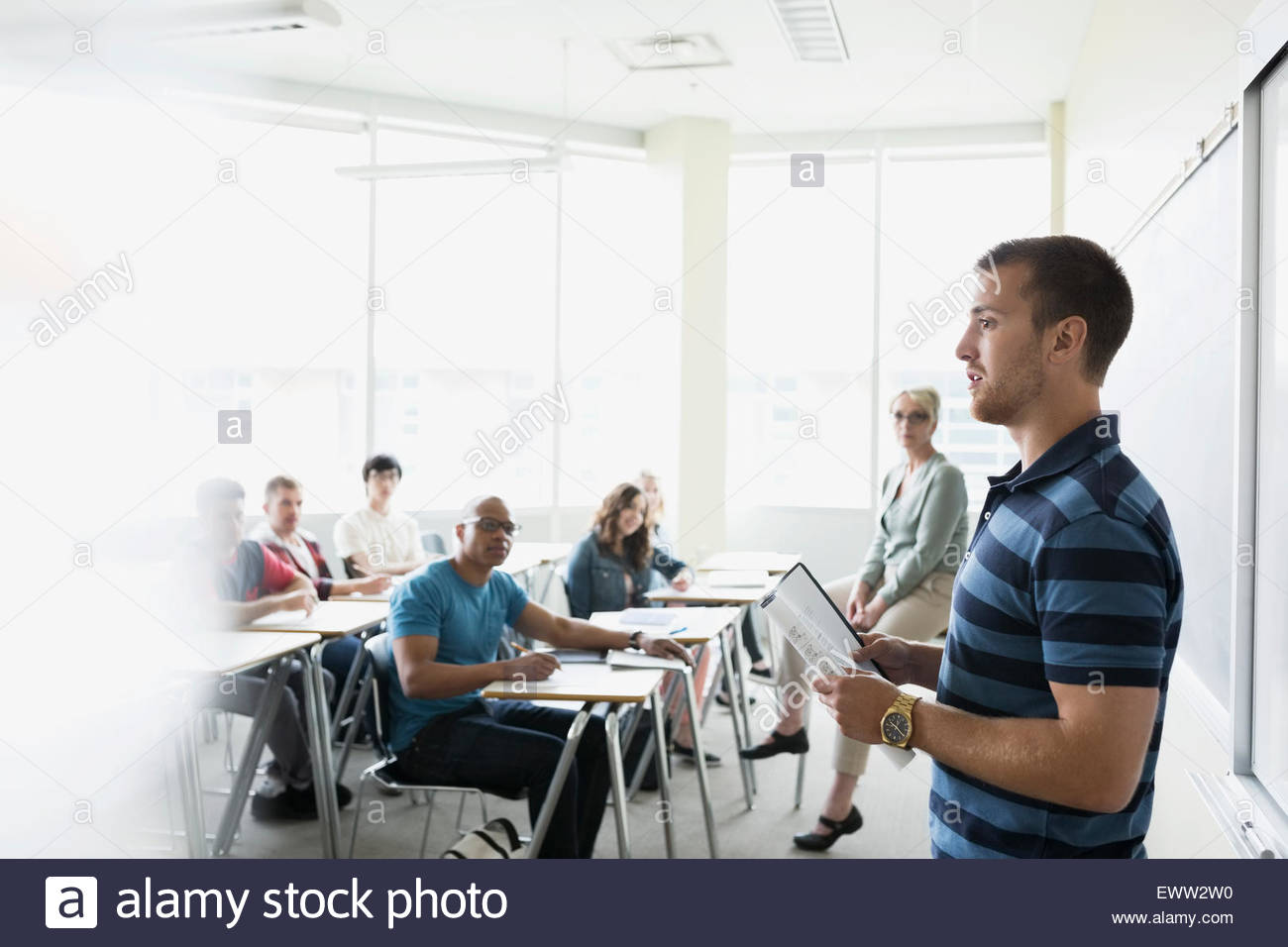 Professor and classmates watching college student give presentation - Stock Image