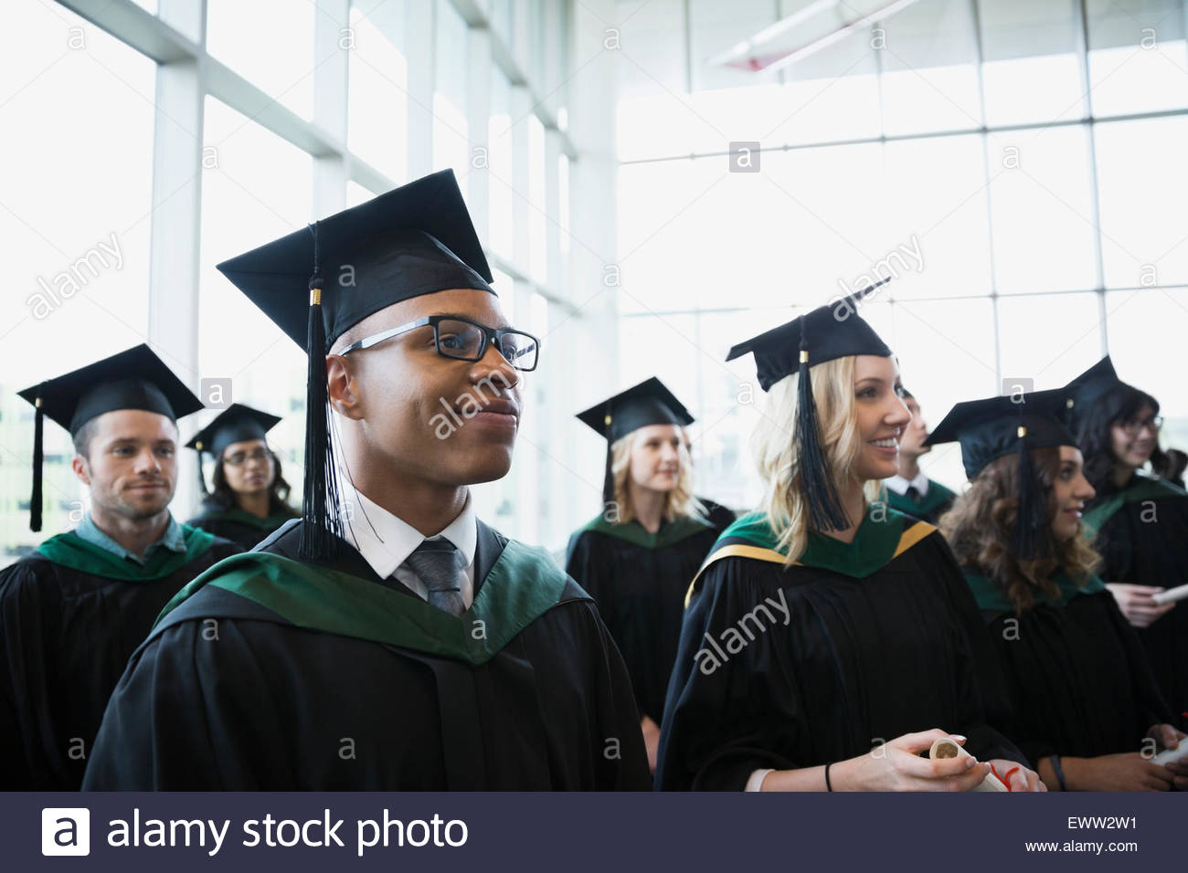 Proud college graduates cap and gown looking away - Stock Image