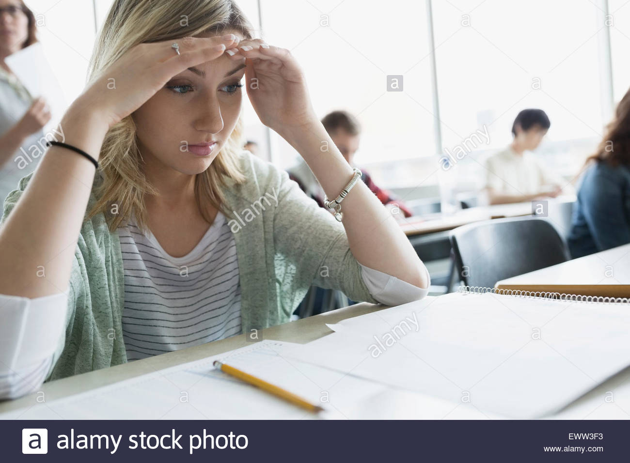 Stressed college student looking down at exam classroom - Stock Image