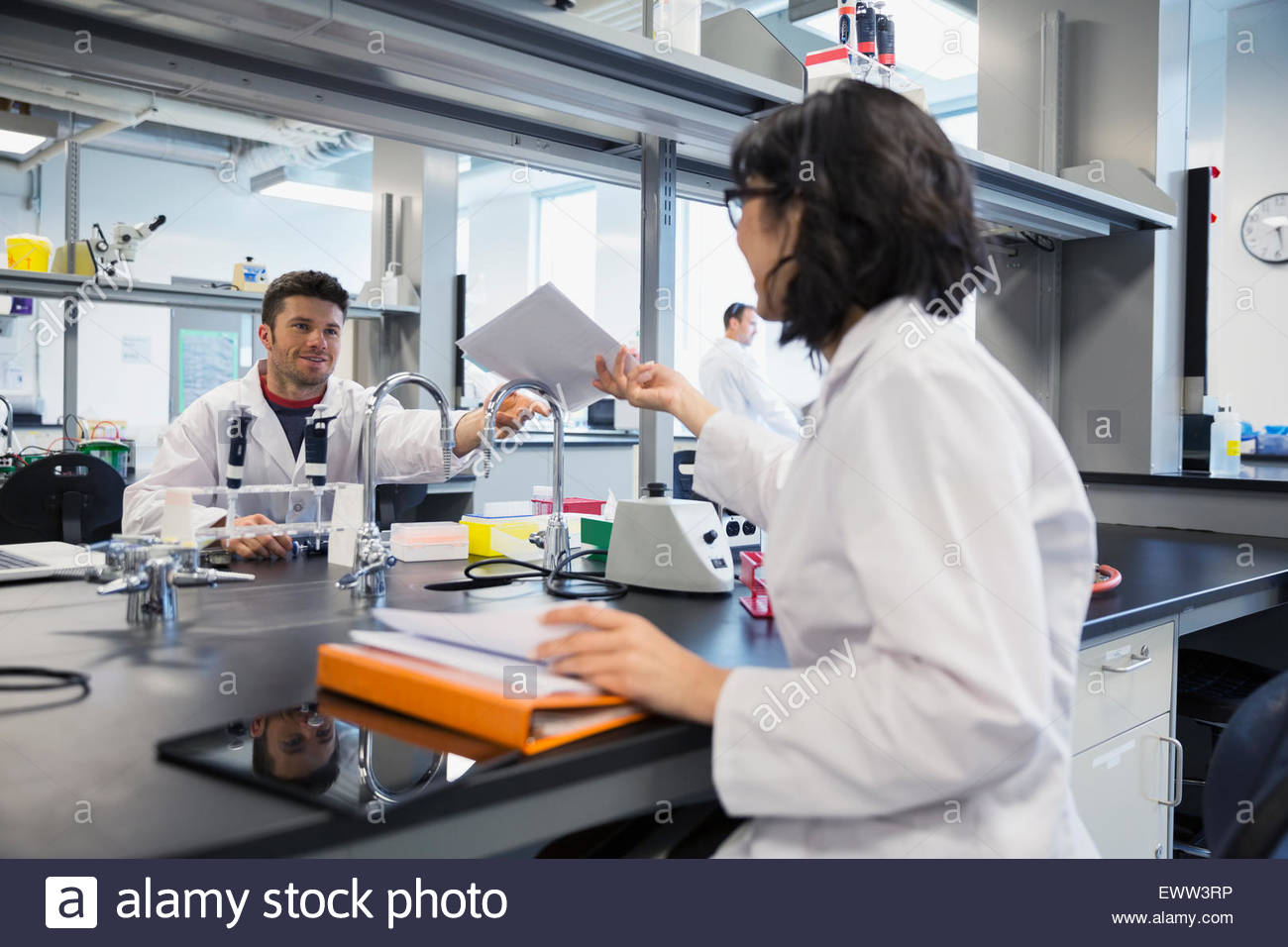 Scientists passing paperwork across laboratory table - Stock Image