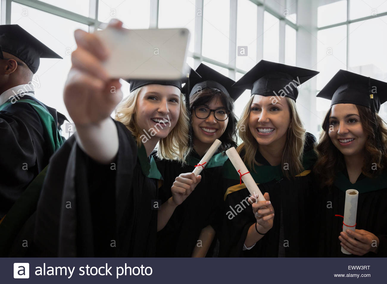 College graduates posing for selfie cap and gown - Stock Image