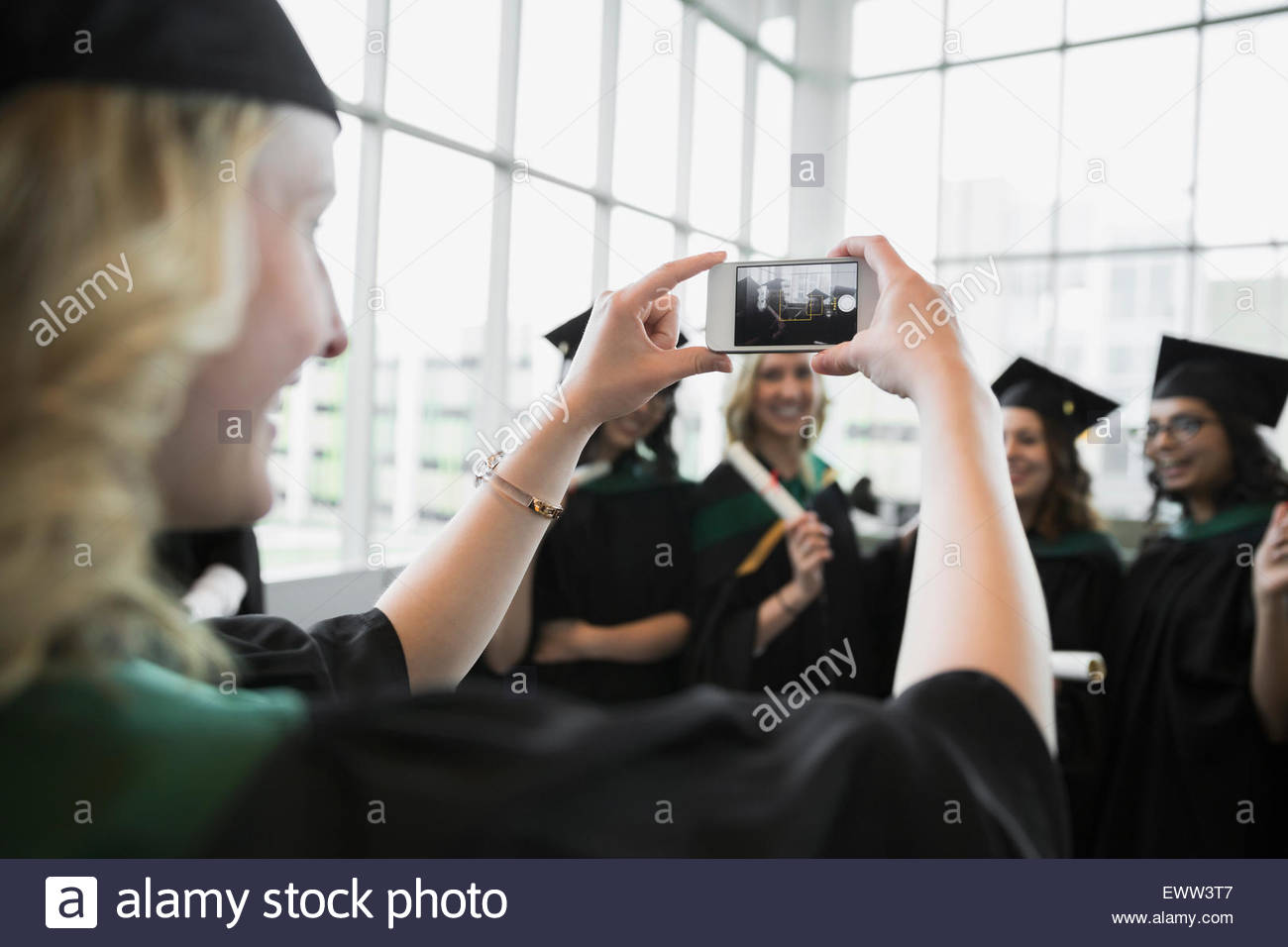 College graduates in cap and gown posing photograph - Stock Image