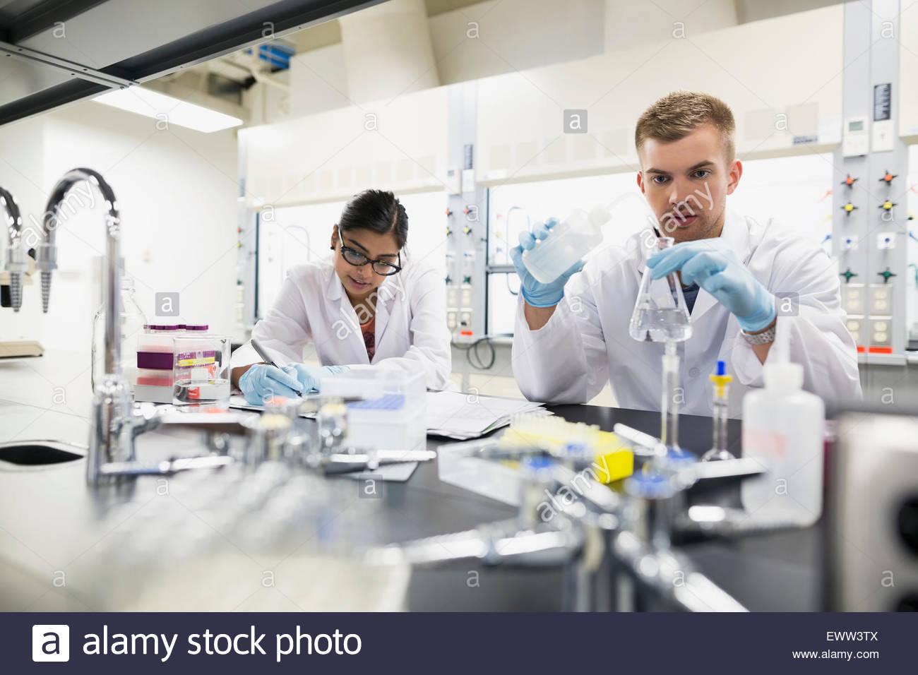 Scientists conducting scientific experiment in laboratory - Stock Image