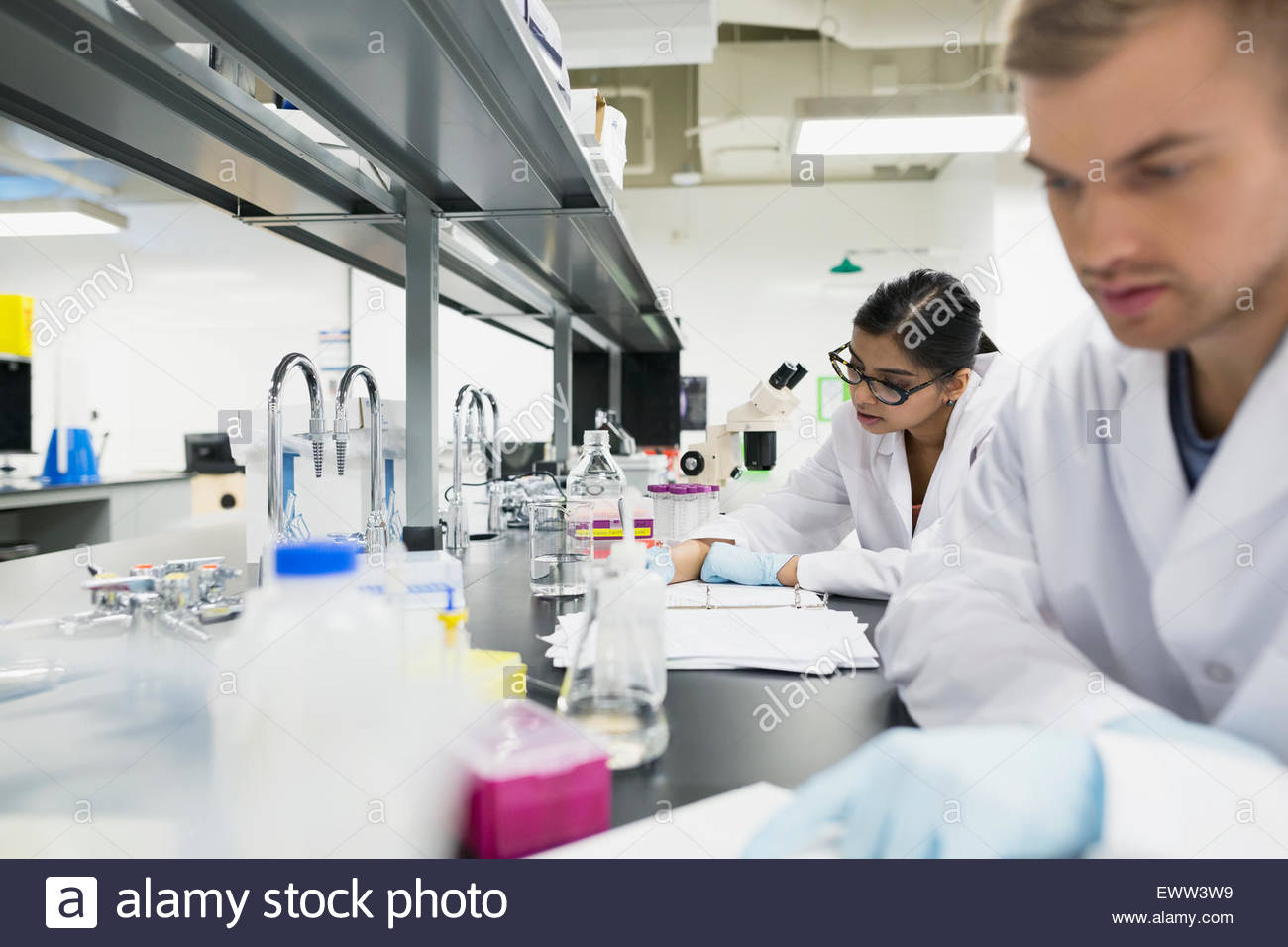 Science students conducting scientific experiment in laboratory - Stock Image