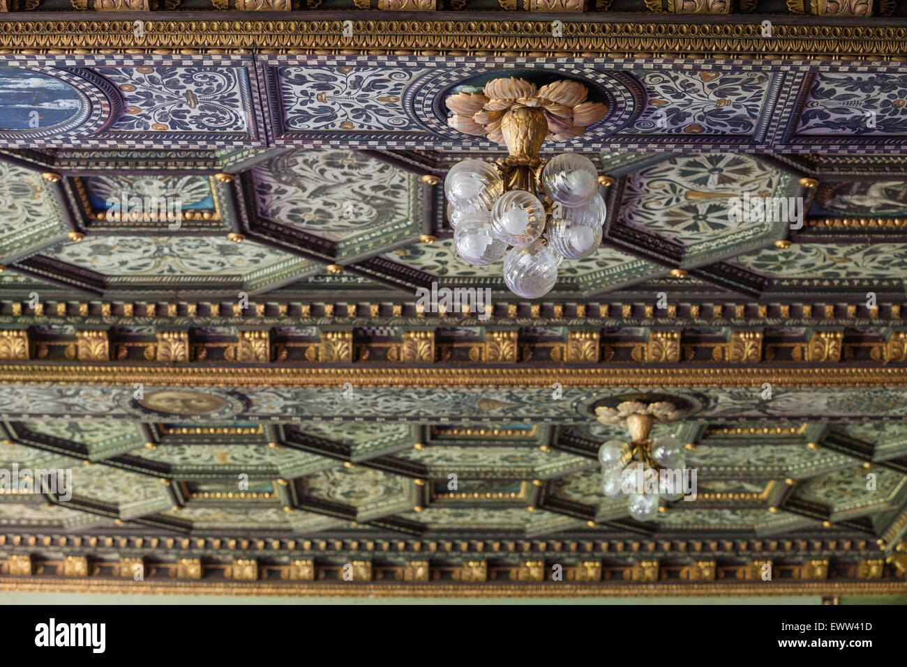 Glass bauble light fitting hung from hand painted gilt stucco coffered ceiling - Stock Image