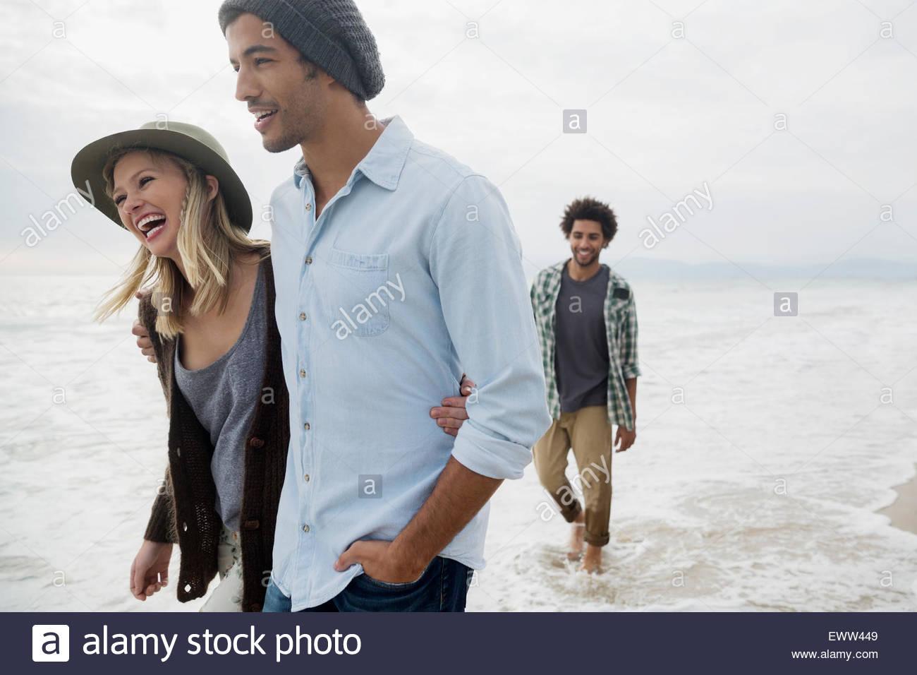 Smiling couple walking in ocean surf - Stock Image