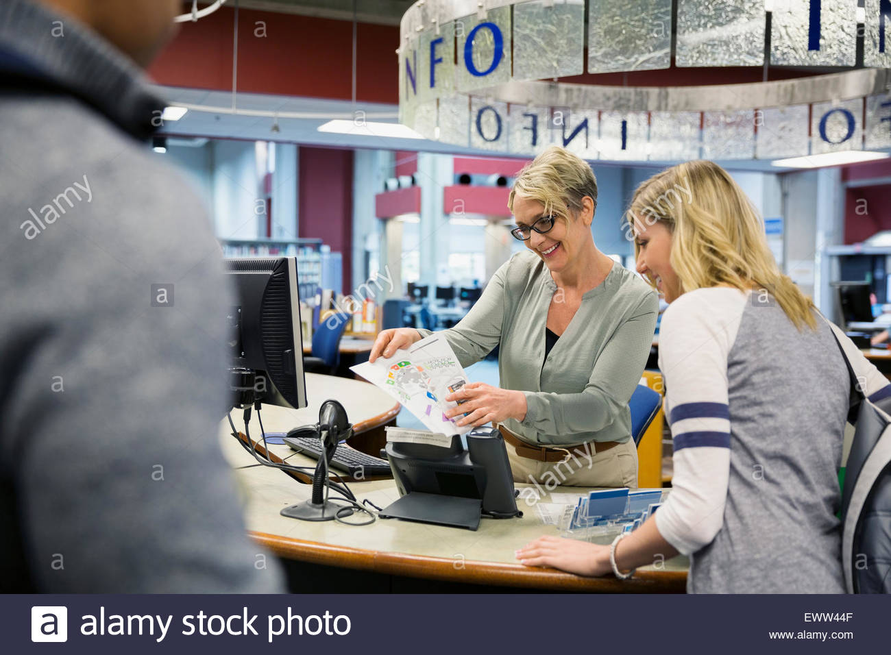 Librarian guiding college student with library map Stock Photo
