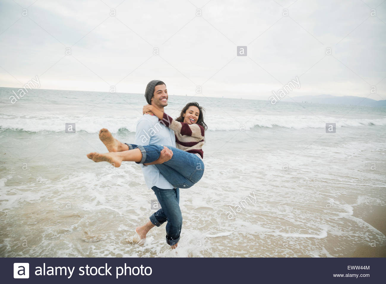 Playful boyfriend carrying girlfriend in ocean surf - Stock Image