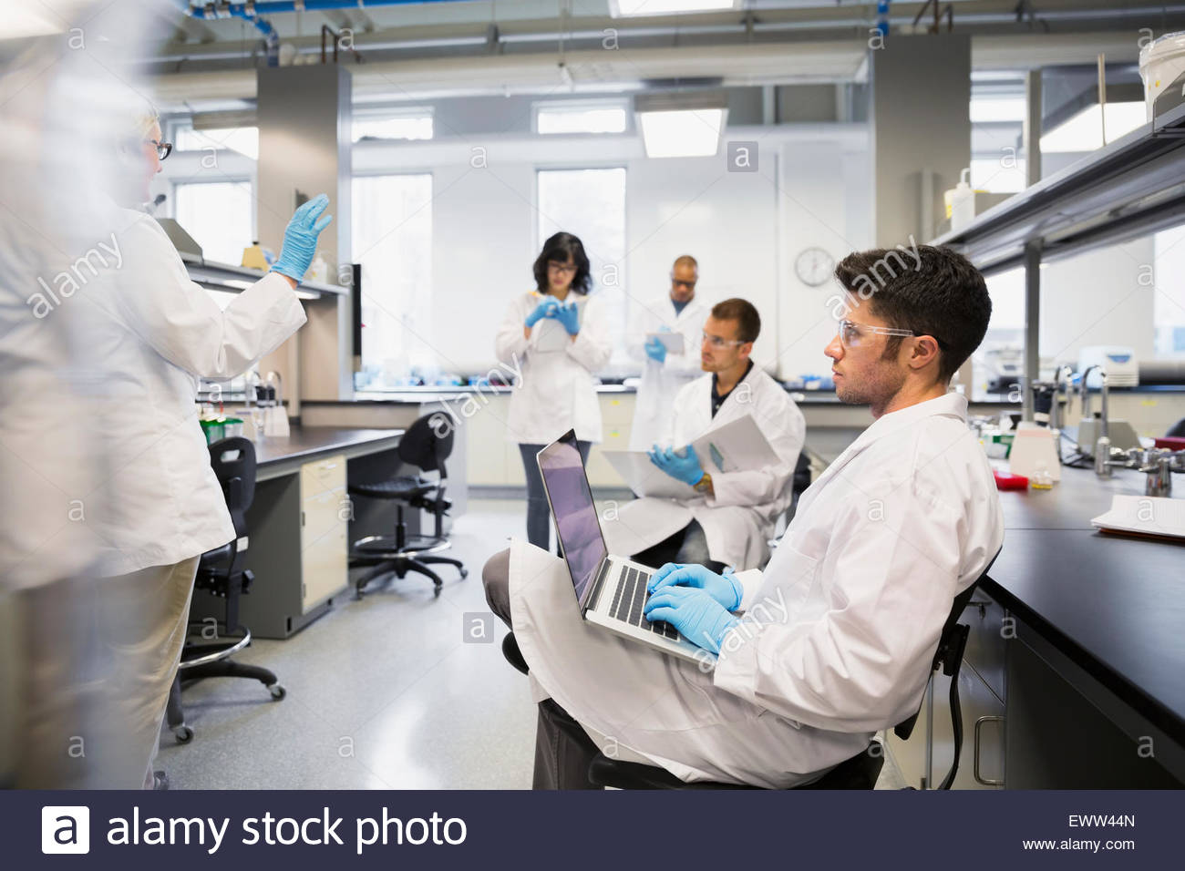 Science students taking notes in laboratory - Stock Image
