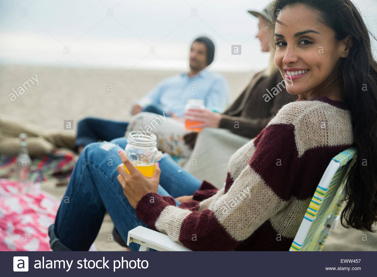 Portrait smiling friend picnicking with friends at beach - Stock Image