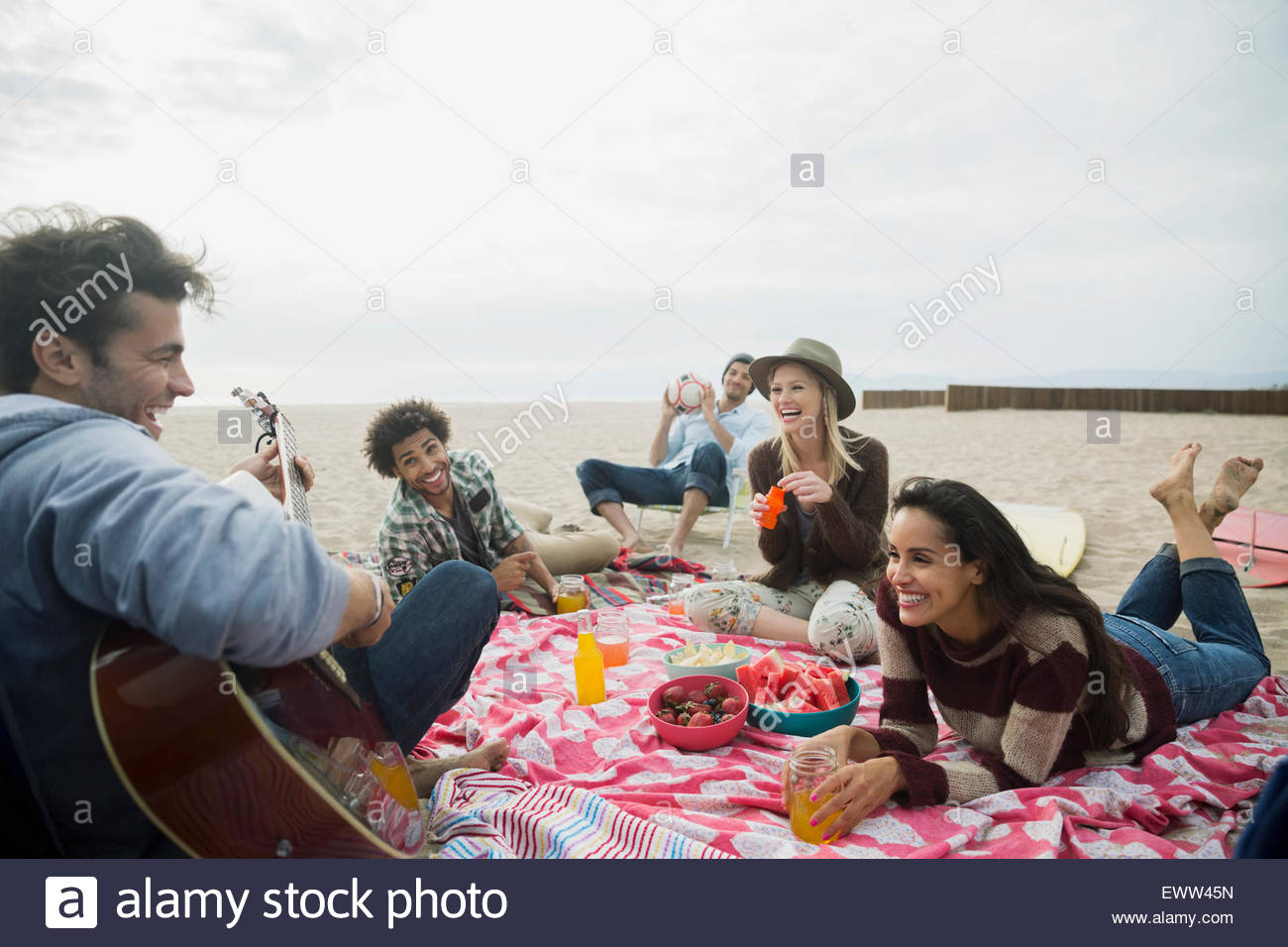 Friends hanging out playing guitar picnicking on beach - Stock Image