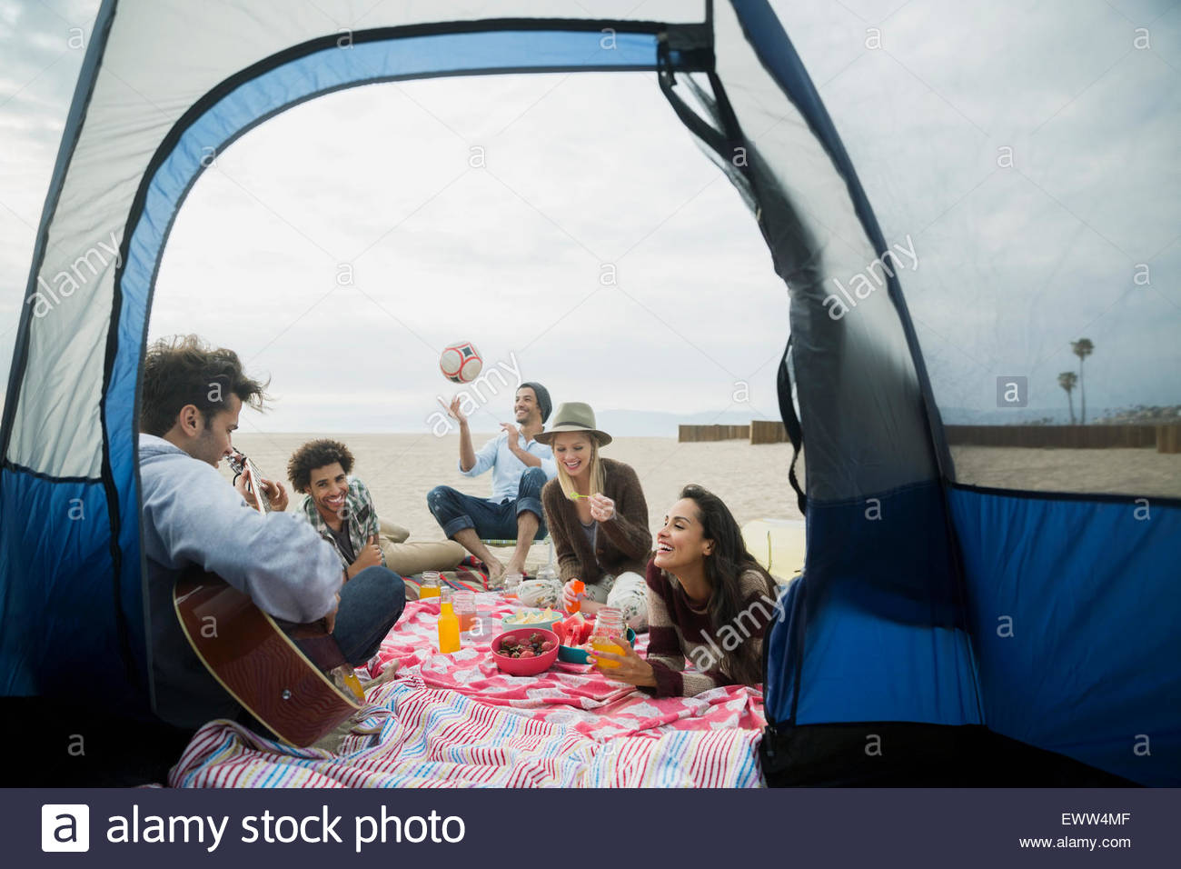 Friends hanging out on beach outside camping tent - Stock Image