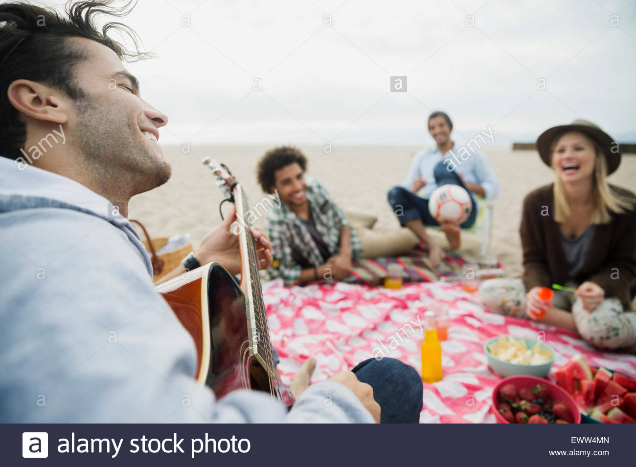 Friends hanging out playing guitar picnicking on beach Stock Photo