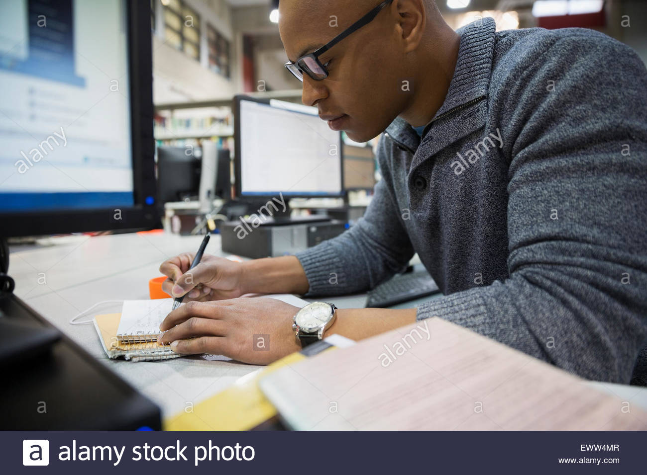 College student studying in library - Stock Image