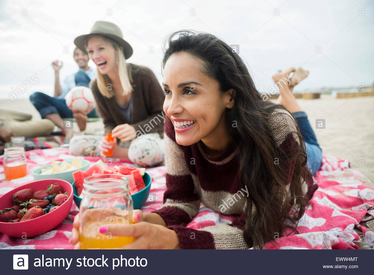Friends relaxing picnicking on beach - Stock Image