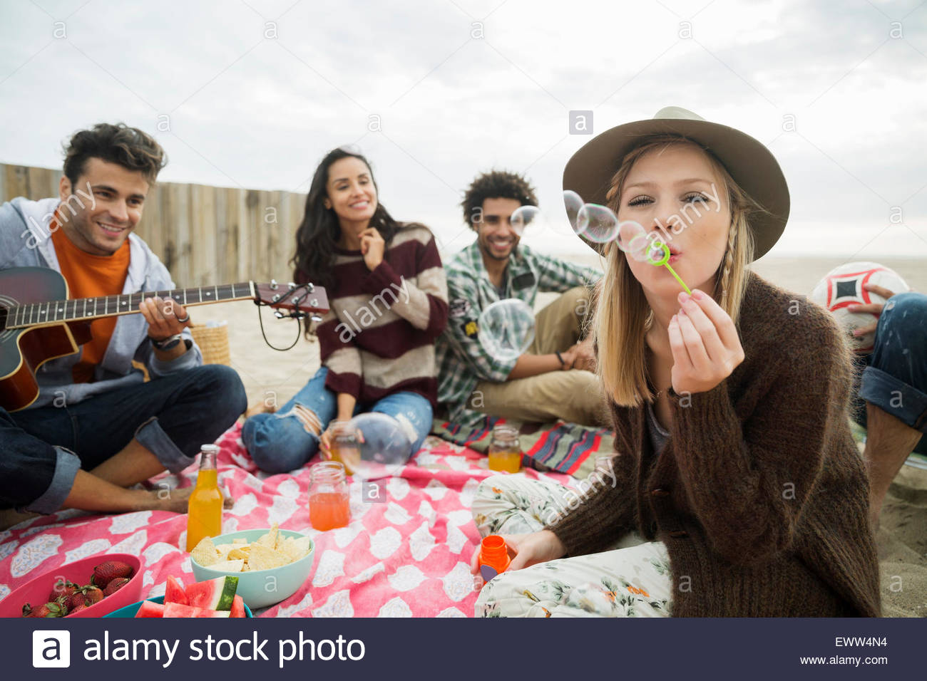 Friends hanging out picnicking on beach - Stock Image