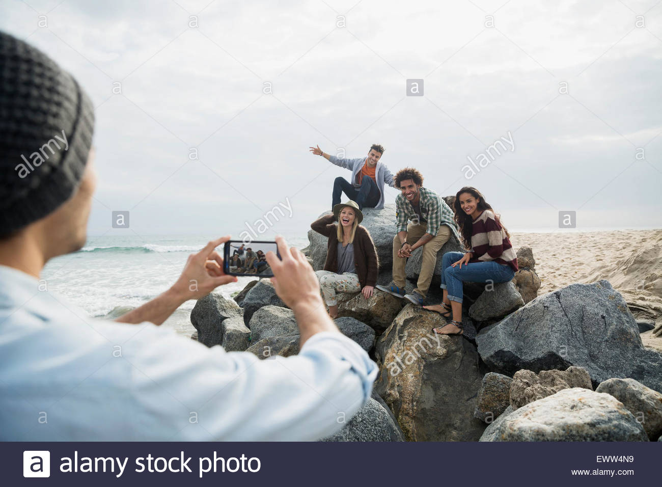 Friends posing for photograph on beach rocks - Stock Image