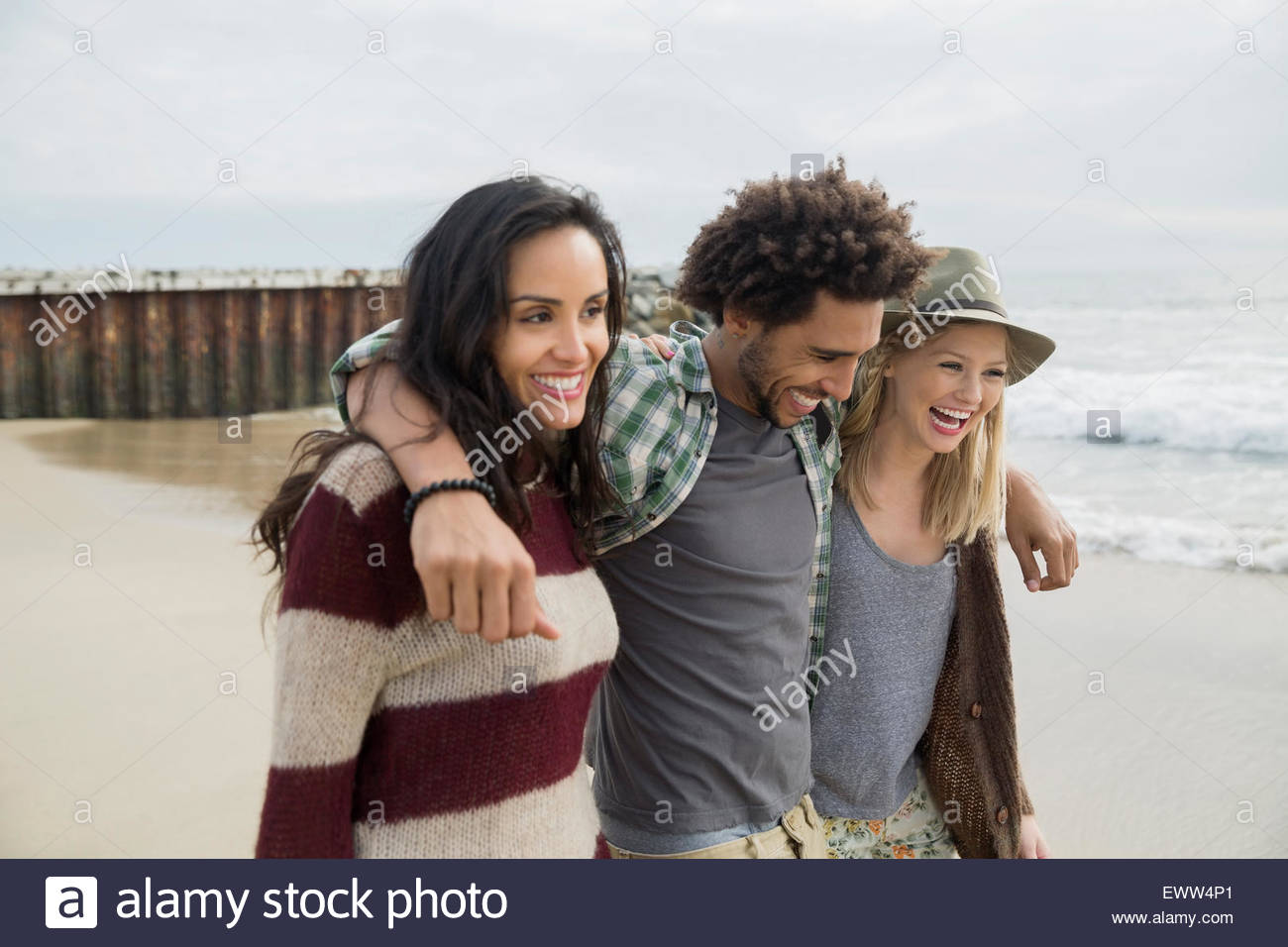 Smiling friends walking in a row on beach - Stock Image