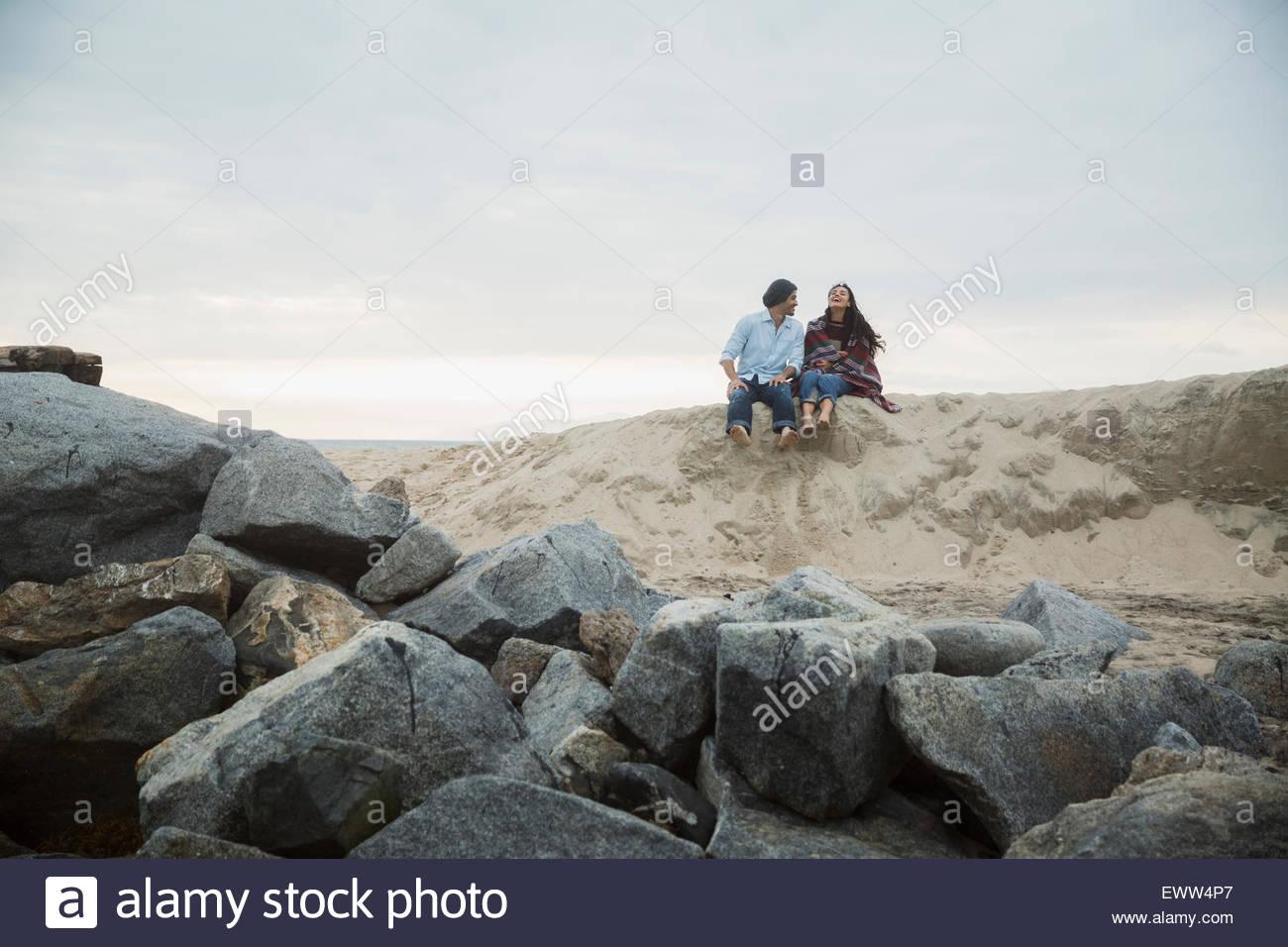 Couple sitting sand hill at beach near rocks - Stock Image