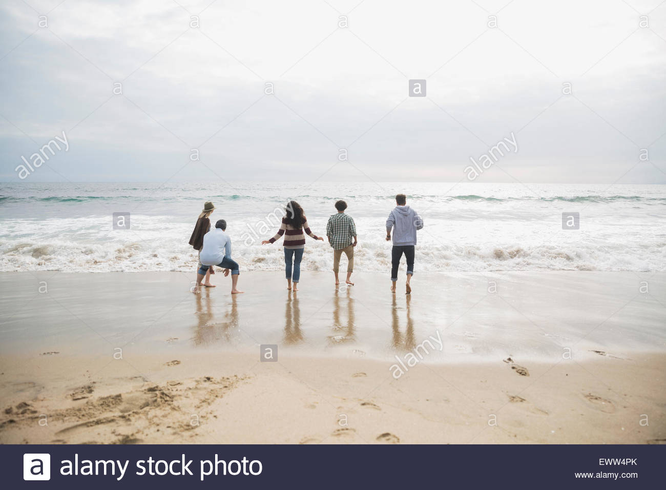 Friends playing in ocean surf at beach - Stock Image