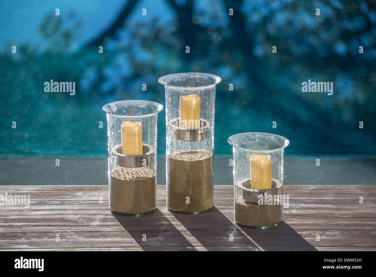 Votive candles suspended above sand in three cylindrical glass vases - Stock Image