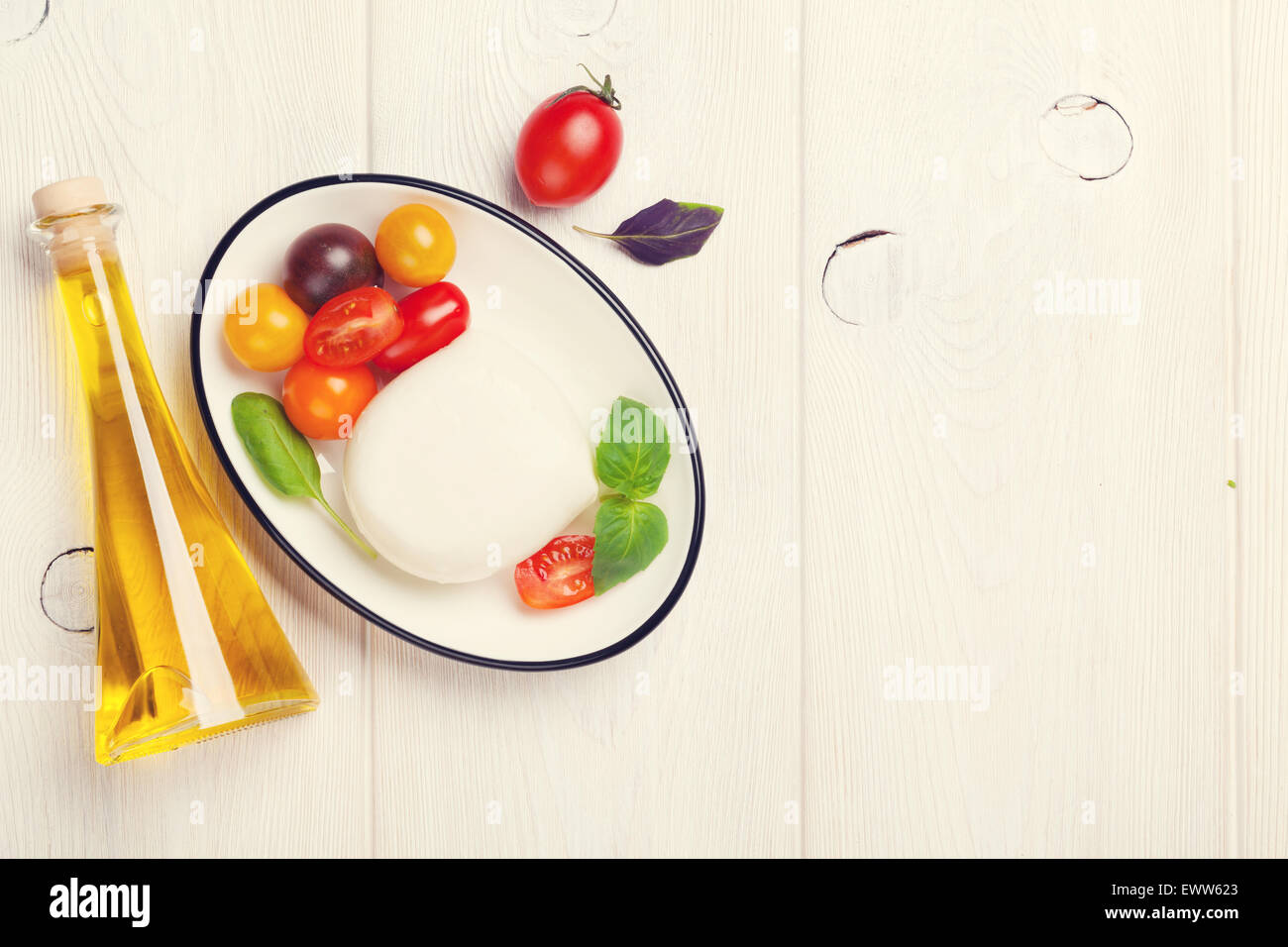 Mozzarella, tomatoes, basil and olive oil on wooden table. Top view with copy space. Toned Stock Photo
