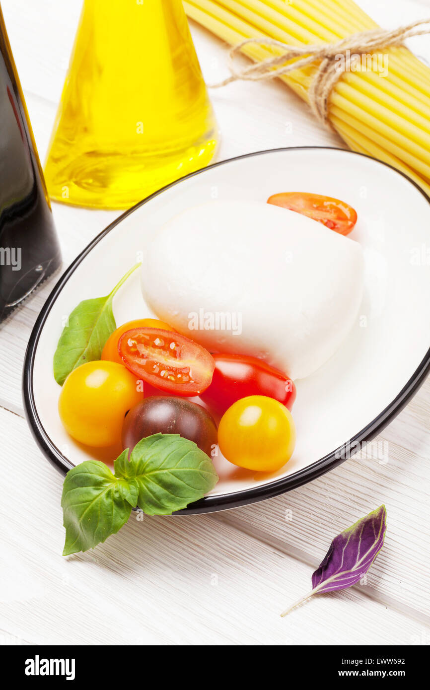 Mozzarella, tomatoes, basil and olive oil on wooden table Stock Photo