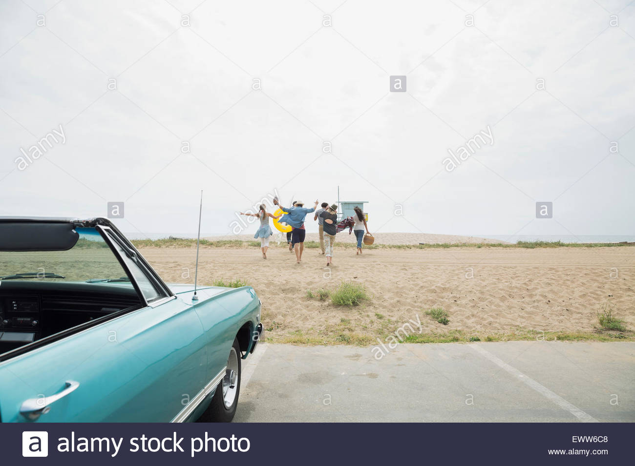 Enthusiastic friends running from convertible onto beach - Stock Image