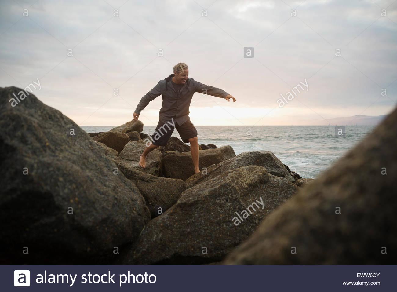 Man stepping on ocean rocks at sunset - Stock Image