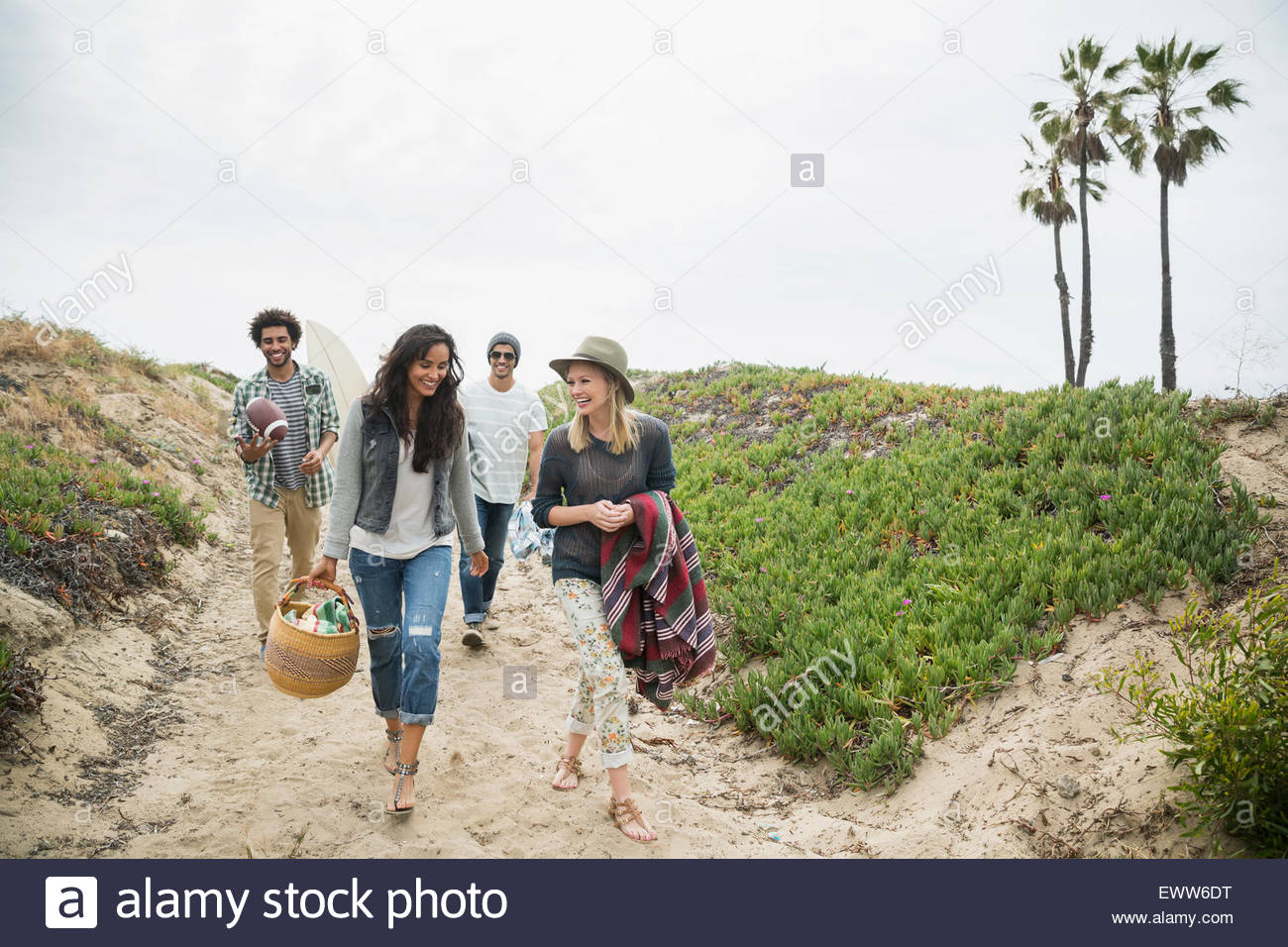 Friends carrying picnic items on beach path - Stock Image