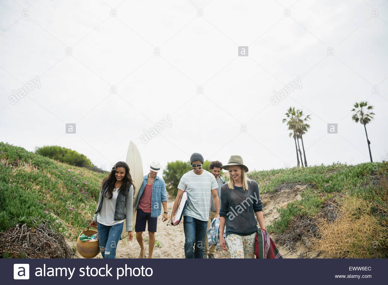 Friends carrying surfboard and picnic items beach path - Stock Image