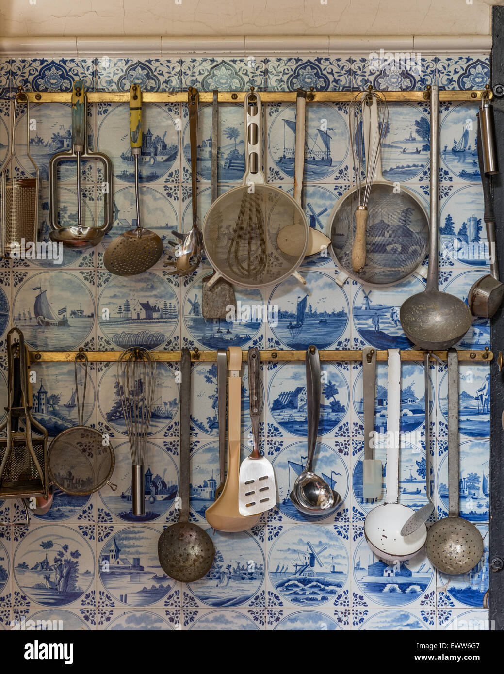 Kitchen utensils hung on rack with delft tiles behind - Stock Image