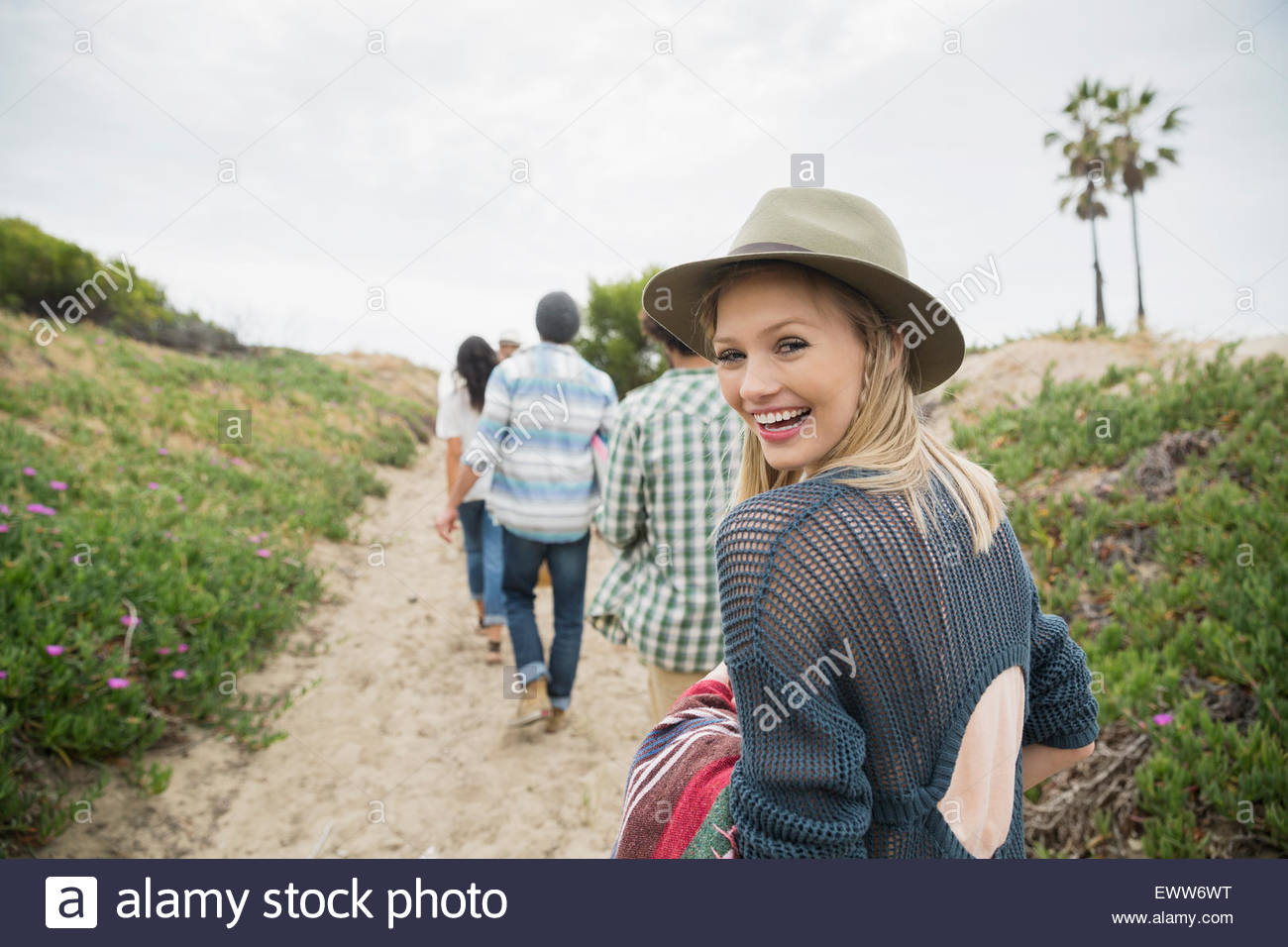Portrait smiling young woman walking on beach path - Stock Image