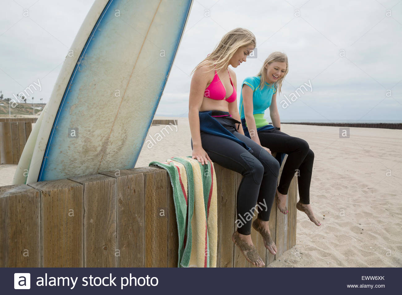 Female surfers taking a break on beach wall - Stock Image