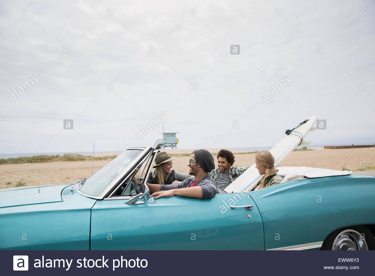 Young couples riding in convertible with surfboard beach Stock Photo