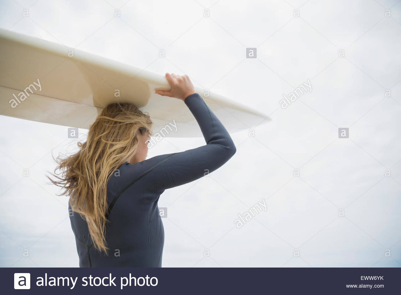 Blonde female surfer carrying surfboard overhead - Stock Image