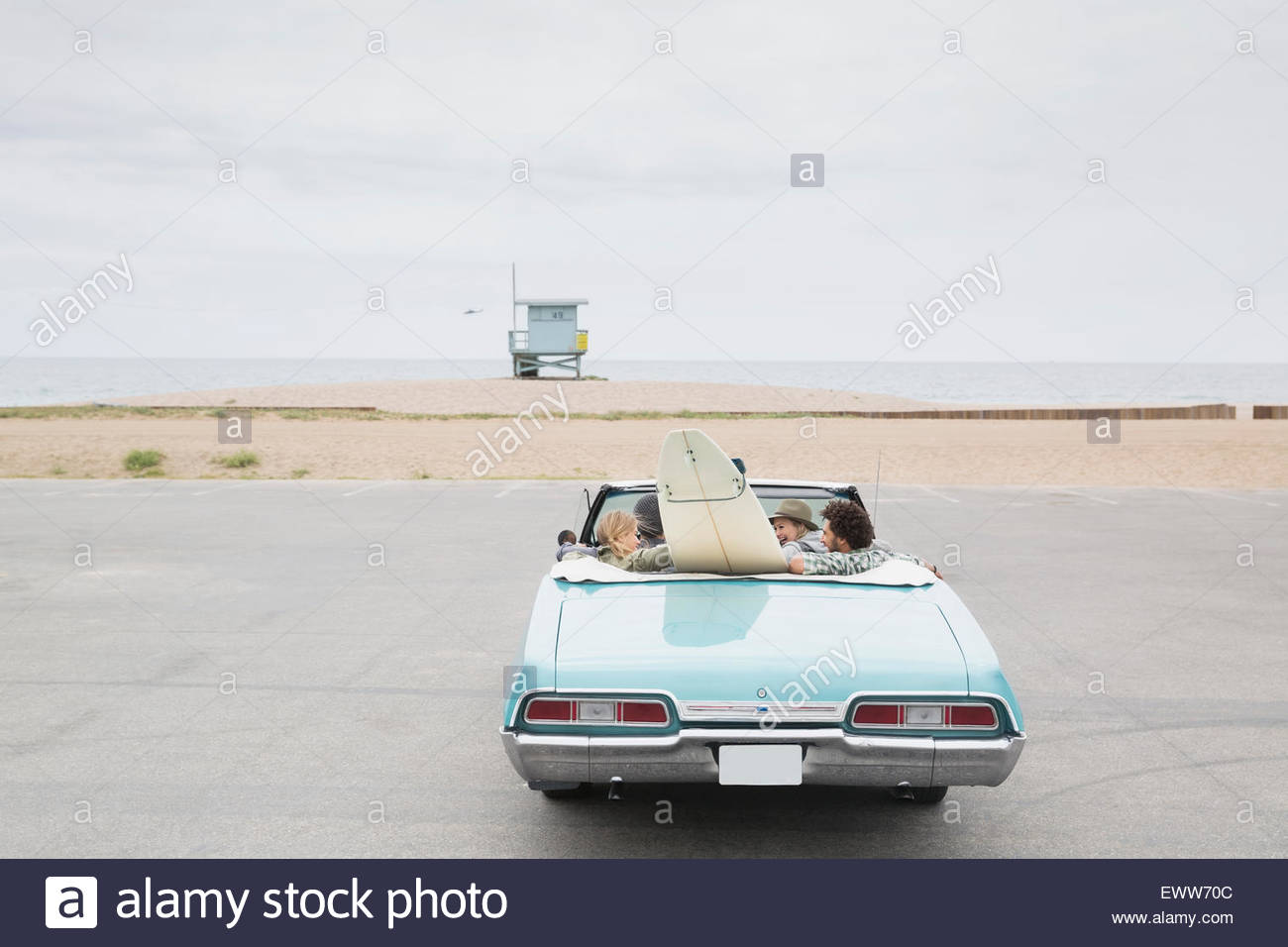 Friends in convertible with surfboard arriving beach - Stock Image