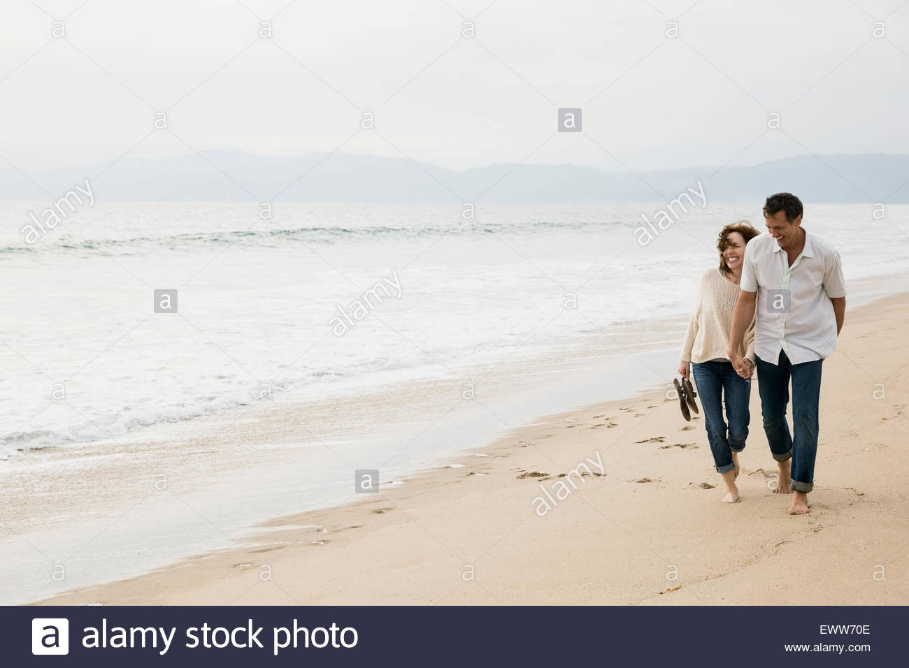 Couple holding hands and walking on beach - Stock Image