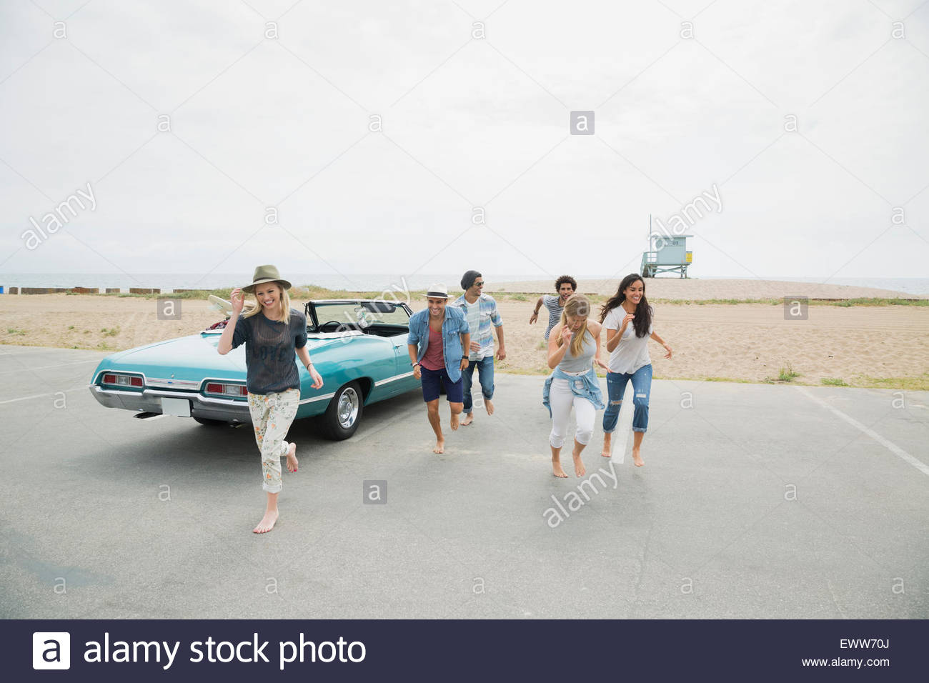 Friends running from beach in parking lot - Stock Image