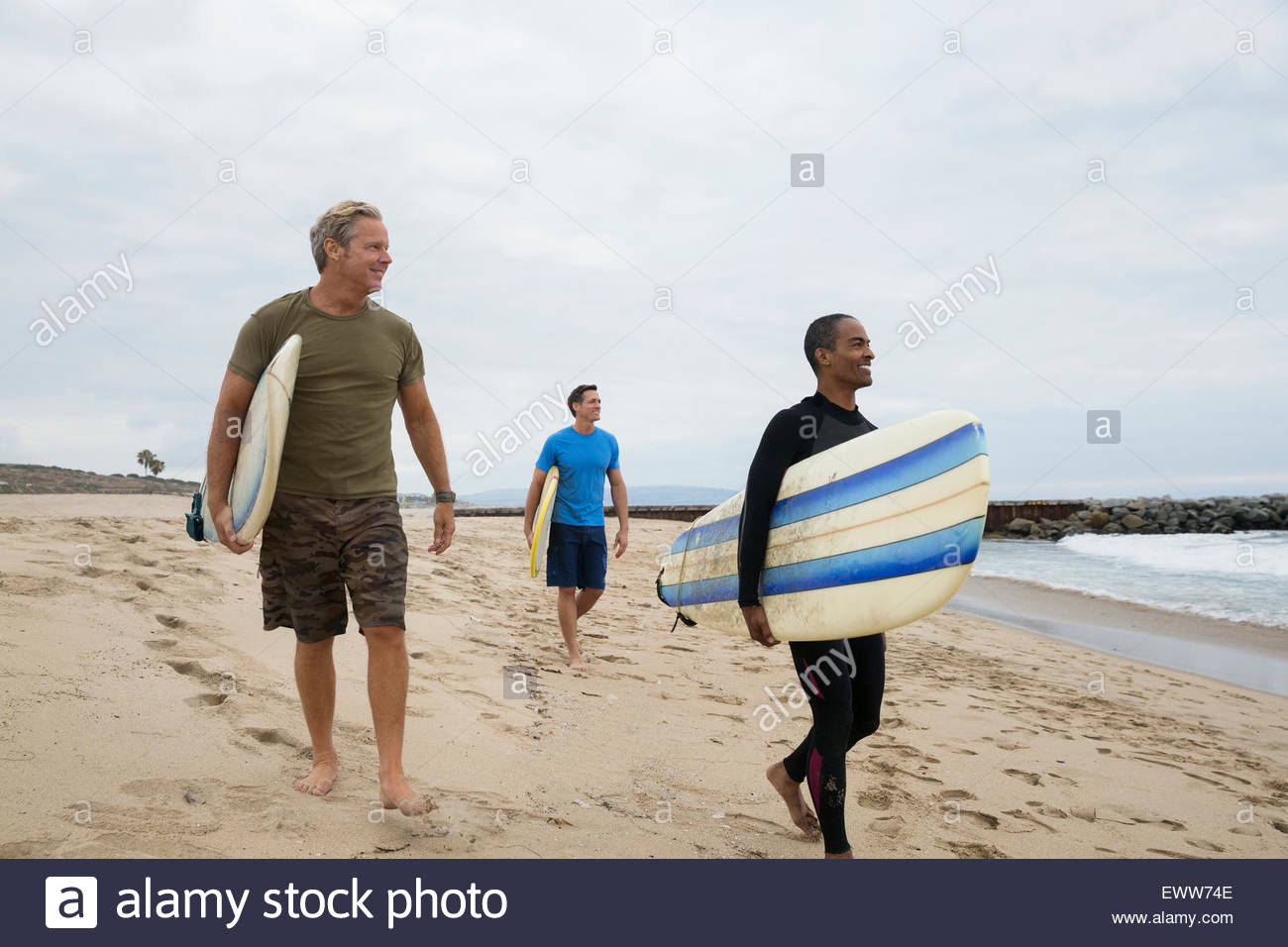 Men with surfboards walking on beach - Stock Image