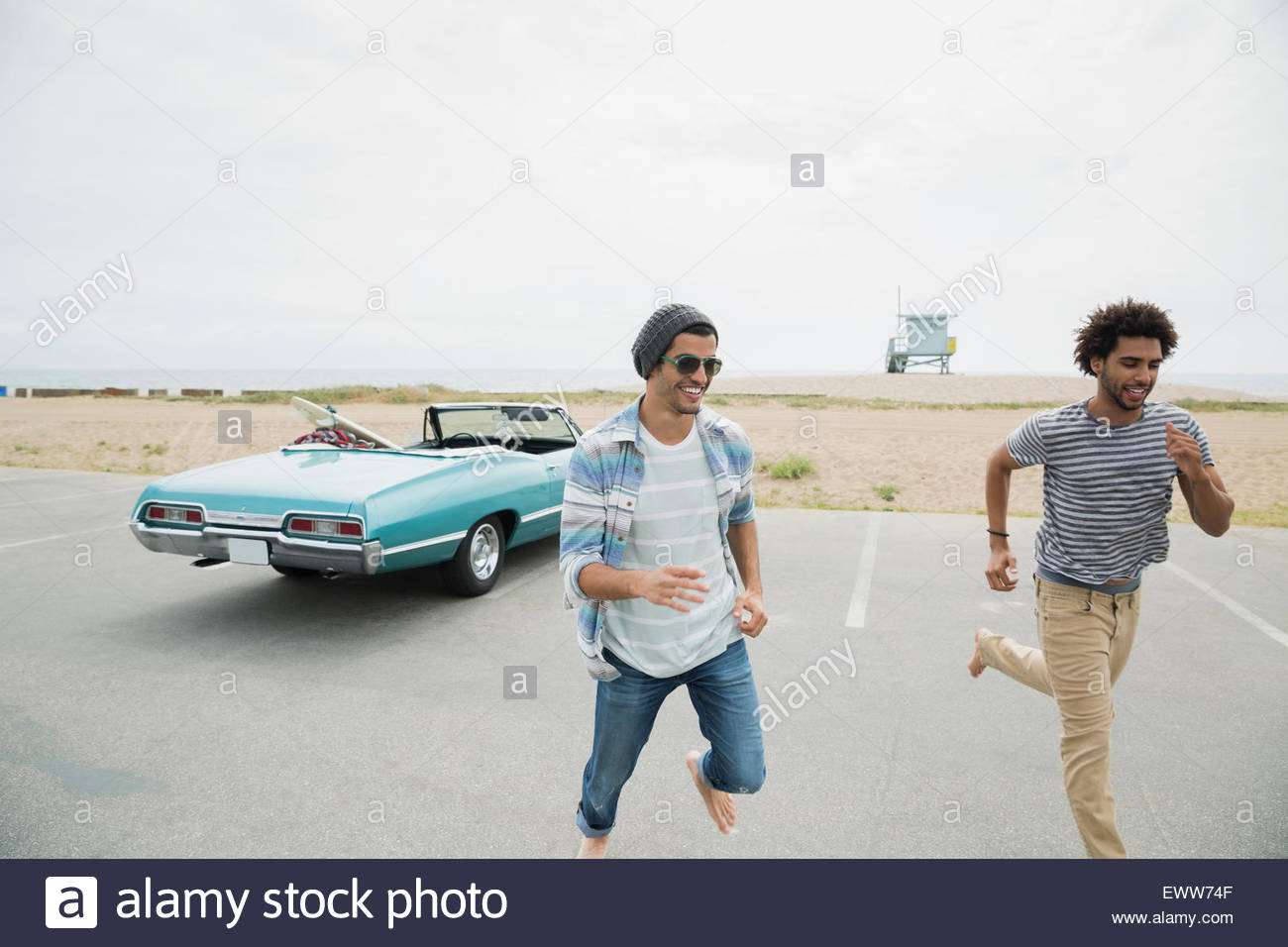 Friends running from beach and convertible parking lot - Stock Image
