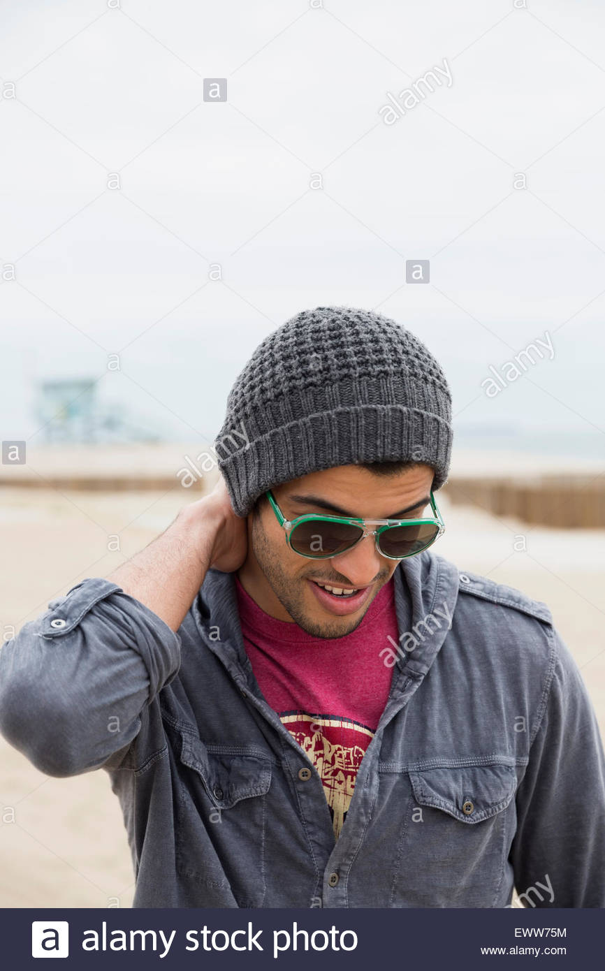 Man in sunglasses and stocking cap at beach - Stock Image