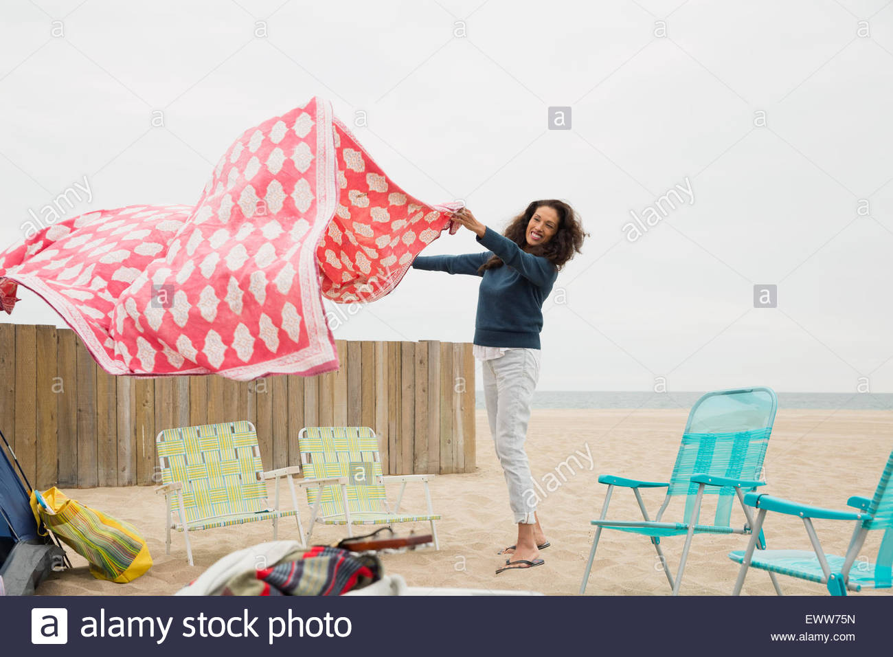 Woman spreading picnic blanket at beach - Stock Image