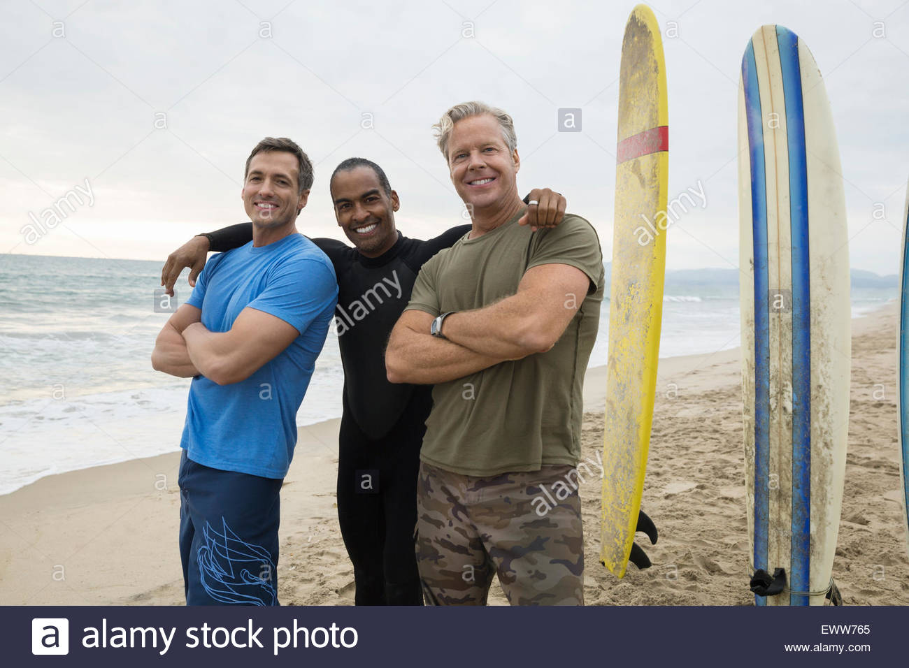 Portrait smiling men with surfboards on beach - Stock Image
