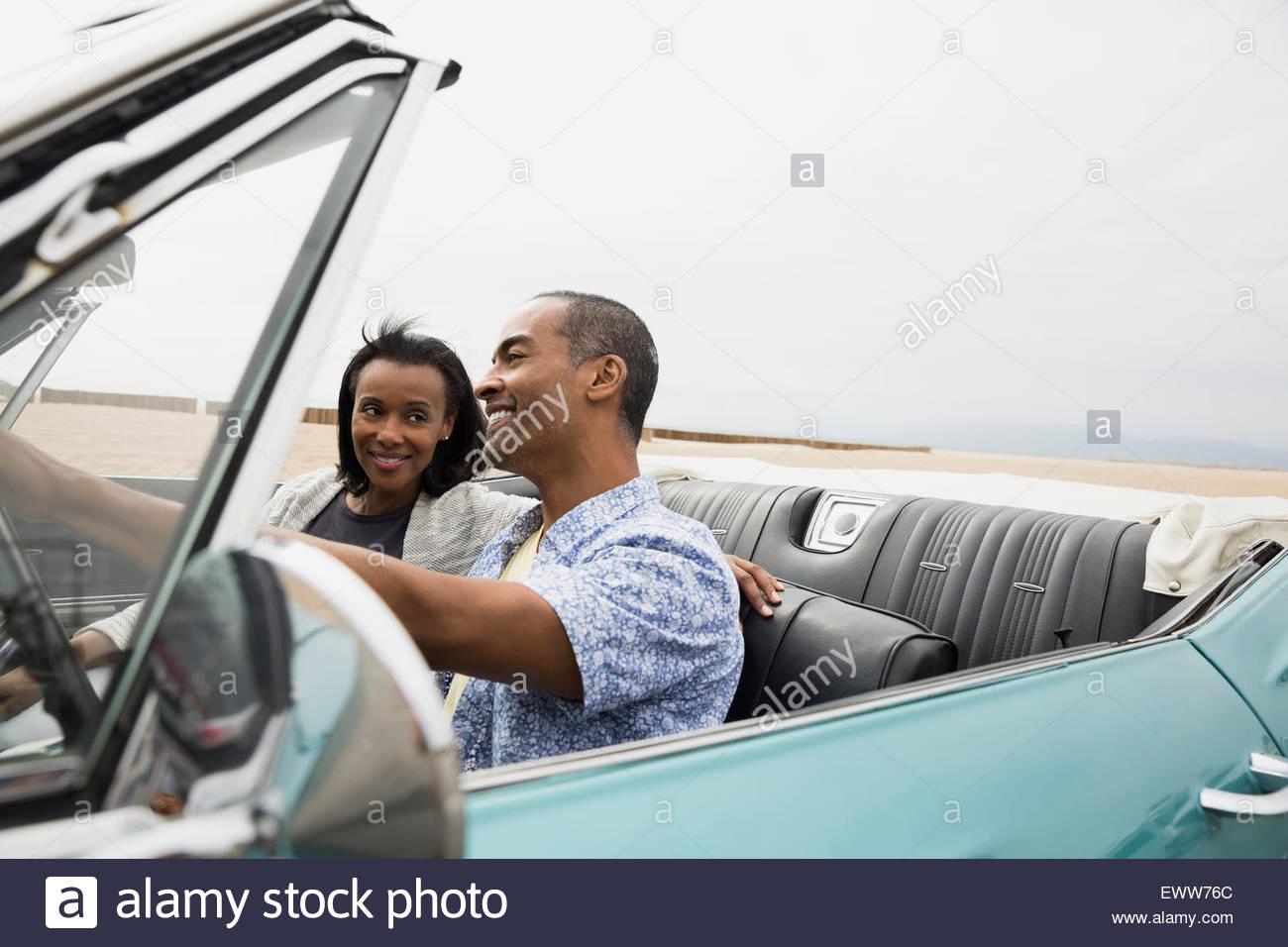 Couple riding in convertible along beach - Stock Image