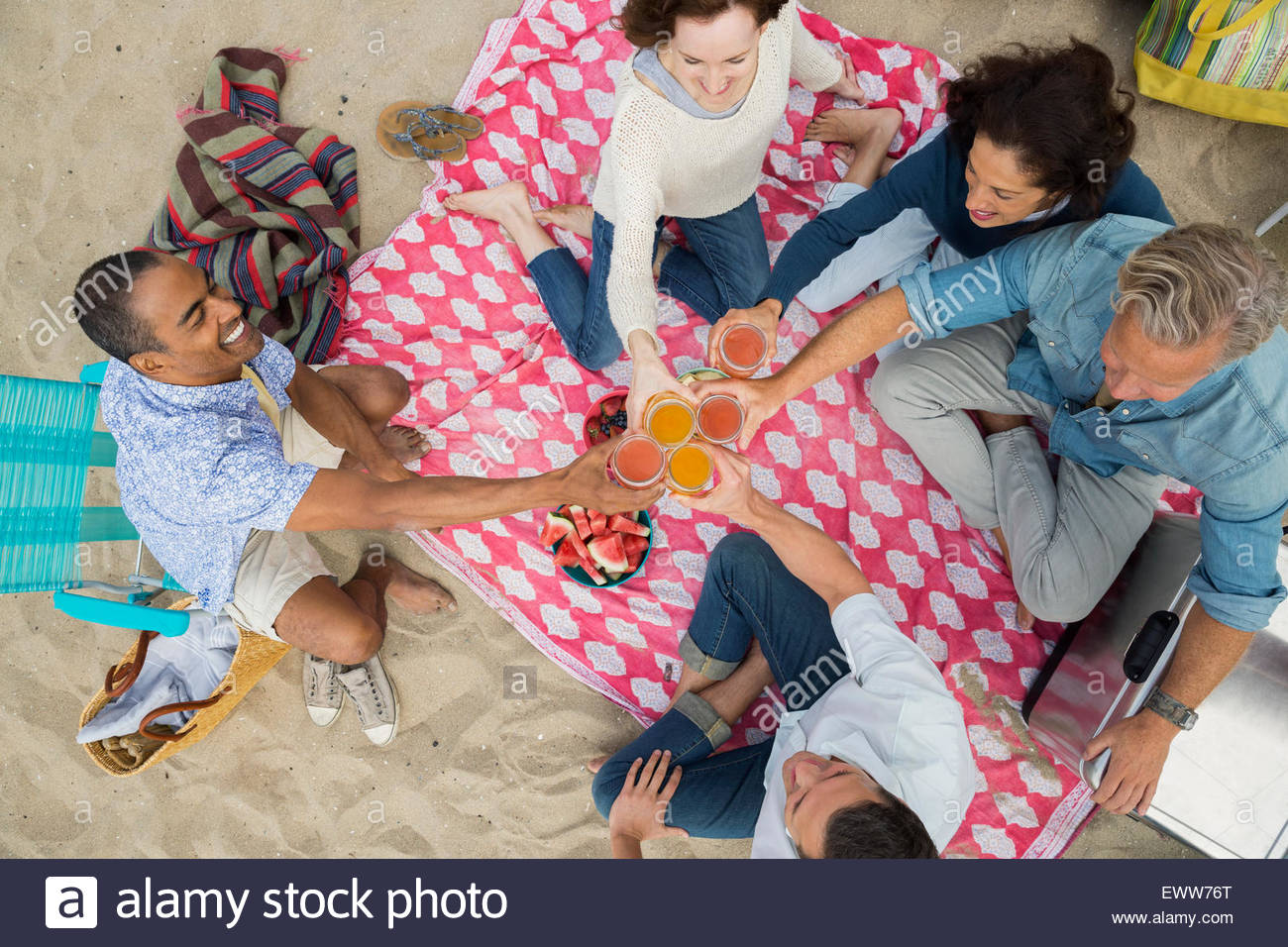 Overhead view friends toasting cocktails at beach picnic - Stock Image
