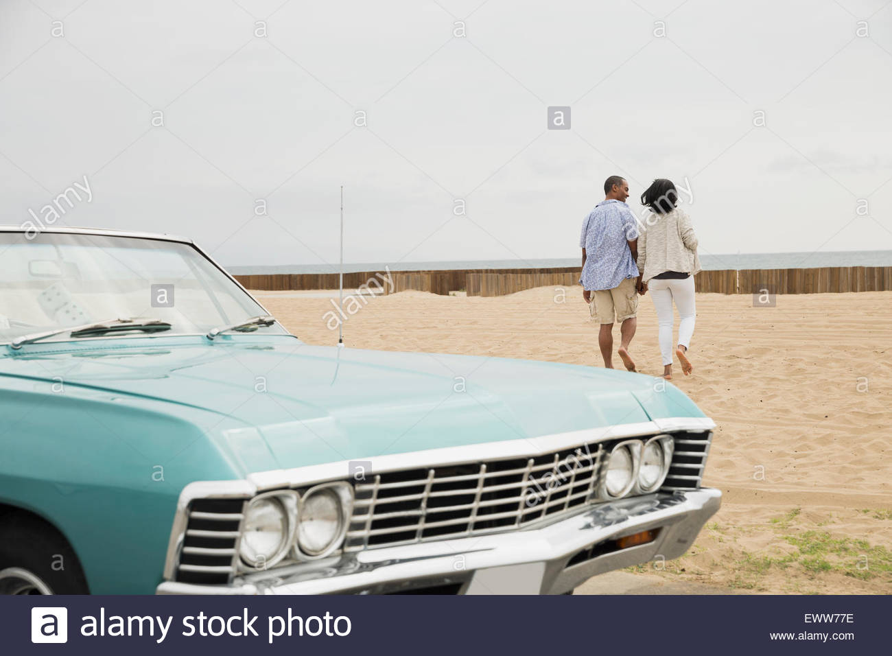 Couple walking from convertible onto beach - Stock Image